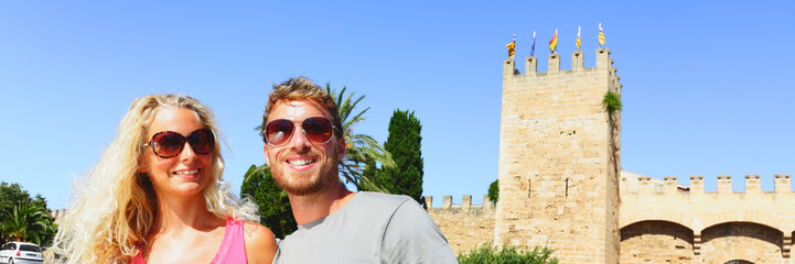 Summer couple on cruise travel wearing sunglasses on Mallorca old town visiting castle outside. Europe vacation banner panorama.