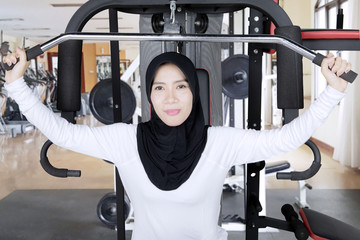 Young Muslim woman with weight machine