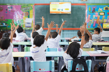 Student hands up asking a question in class at the elementary school. Education concept.