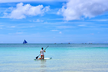 Woman is enjoying a view in standup paddleboarding over the ocean