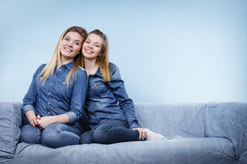Two happy women friends wearing jeans outfit poitning