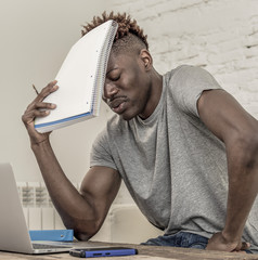 young desperate and overwhelmed black afro American student man in stress at home working stressed with laptop computer worried and tired