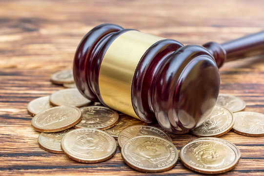 Judge's gavel with coins on the table. Close up.