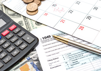 Tax form with calculator, pen and calendar on the background of money. Tax time.