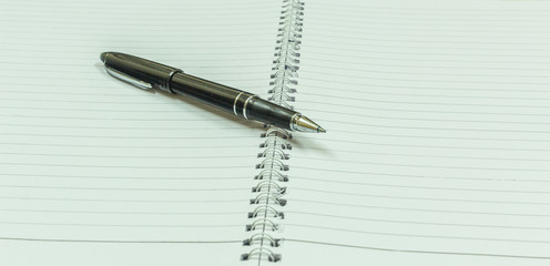 Image depicting blank spiral notebook with a black vintage pen placed over for financial investments or calculation. With selective focus on the subject.