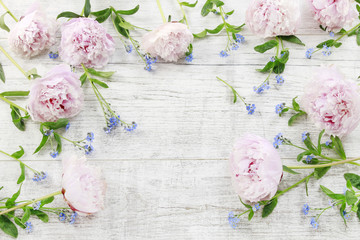 Pink peonies and forget me not flowers on white wood