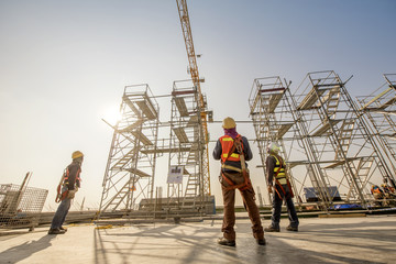 Obraz Construction engineers supervising progress of construction project stand on new concrete floor top roof and crane background - fototapety do salonu