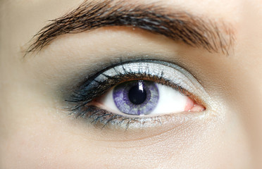 Violet eyes (mutation eyes), Close Up. The human eye of a woman with light beauty cosmetics and long natural eyelashes. Girl with perfect skin
