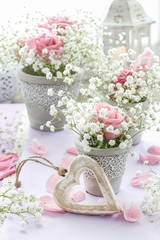 Floral arrangement with pink roses, gypsophila paniculata and candles.
