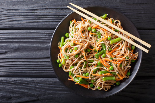 Japanese soba salad with vegetables and sesame close-up on the table. horizontal top view