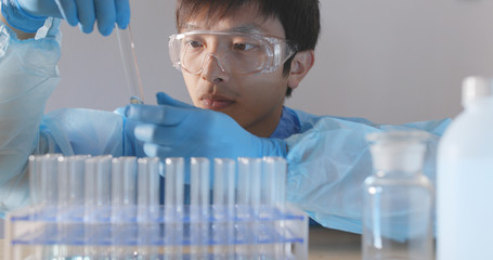 Researchers working on test tube in laboratory