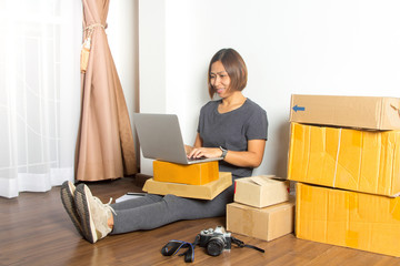 Women working laptop computer from home on wooden floor with postal parcel, Selling online ideas concept