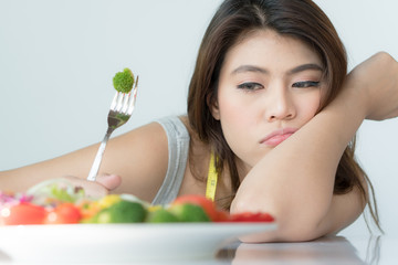 unhappy asian women is on dieting time looking at broccoli on the fork. girl do not want to eat vegetables and dislike taste of broccoli.