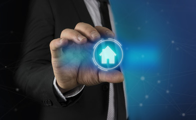 To a man in a suit and tie appears in his hands a futuristic graphic of the house. Concept of: home automation, home applications, and future