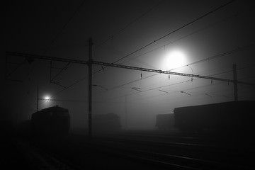 black night on a freight train station in Chomutov city with outlines of railway objects and trains