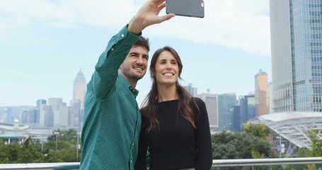 Caucasian woman receiving flower bouquet from his boyfriend and taking selfie by mobile phone