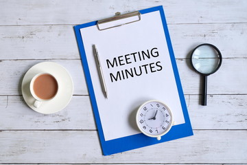 Top view of clipboard with paper written 'MINUTES MEETING' with magnifying glass,pen,table clock and a cup of coffee on white wooden background.