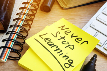 Never stop learning written on a memo stick. Lifelong learning concept. Fotomurales