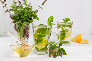 Two glass cups fresh mint tea with lemon and a bunch of mint in vase
