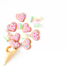 Gingerbread cookies with pink glaze and marshmallow in waffle cone on withe background. Valentines day concept. Flat lay. top view.