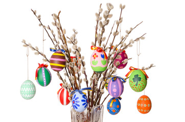 Colored easter eggs on willow bouquet with pussy willows. Religious decoration. Paschal eggs on branches with furry catkins in crystal vase. Salix. Front view, horizontal, on white background. Photo.