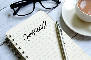 Pen,sunglasses,a cup of coffee and notebook written with 'QUESTIONS?' on white wooden background.