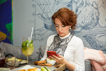 Lunch time. Beautiful adult businesswoman looking at mobile phone in restaurant.