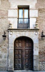 Portal with porch and balcony of an old house with wooden door reinforced by nails that were used for the entrance of carriages in the house and wrought iron balcony ty