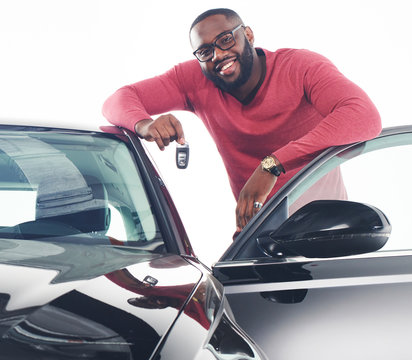 Happy handsome african man showing car keys in near his newly bought vehicle car smiling cheerfully copyspace owner ownership sales driving consumerism private taxi concept studio shot