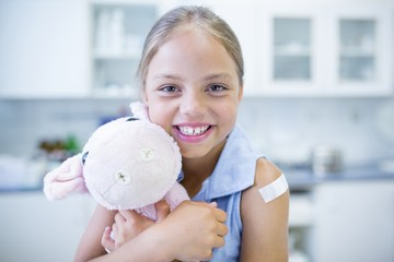 Girl with plaster on arm hugging teddy