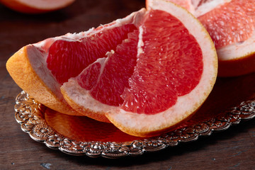 Slices of fresh ripe grapefruit on wooden table.