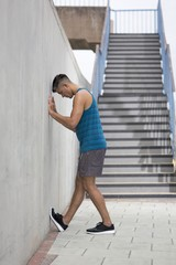 Young man stretching leg against wall