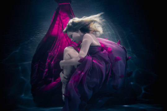 Beautiful woman swimming with fancy dress underwater
