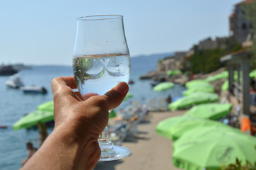 Hand holding a glass of cold fresh mineral water and a beach in background