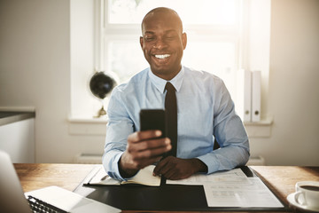 Young businessman smiling at a text on his phone
