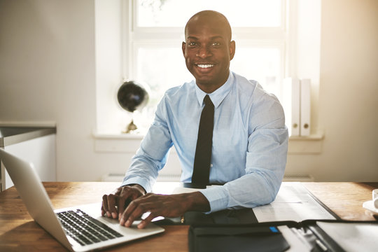 Smiling young businessman working on a computer at his desk