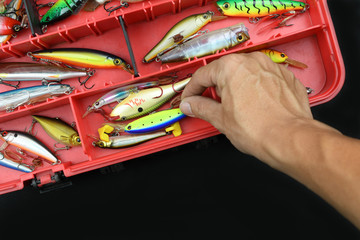 Fisherman is taking lures from the box.