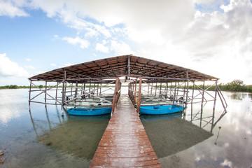 Bootssteg mit kleinen Angelbooten und Außenboardmotoren in Kuba