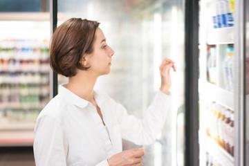 店舗で飲み物を選ぶ女性