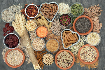 Foto auf Leinwand Sortiment Healthy high fibre dietary food concept with whole wheat pasta, legumes, nuts, seeds, cereals, grains and wheat sheaths. High in omega 3, antioxidants, vitamins. On marble background top view.