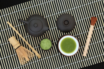 Japanese green matcha tea with powder and drink in a cup with whisk, brush and scoop on bamboo background. Health drink concept.