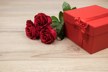 Red roses and gift box on wooden table, valentines Day, wedding day concept