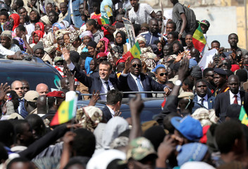 French President Emmanuel Macron and Senegalese President Macky Sall wave to the crowd from their motorcade in Saint-Louis