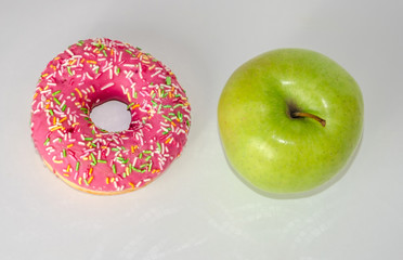 donut and green apple on white table