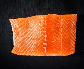 Raw salmon fillet on black stone