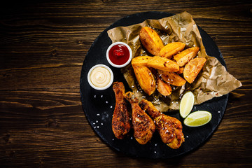Grilled drumsticks with French fries wooden background