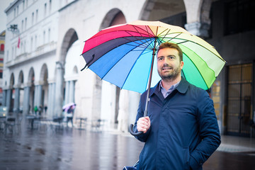 Rainy day in the city and businessman holding umbrella