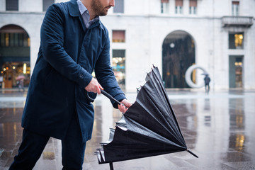 Rainy day in the city and businessman opening umbrella