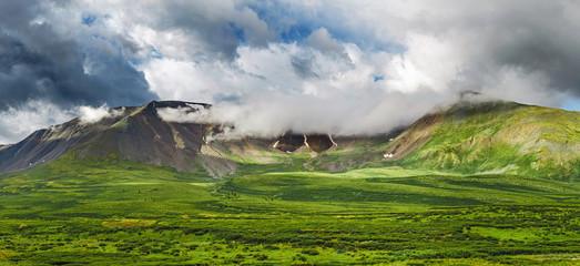 A classic Altai landscape with snow-capped rocky mountains and vast pastures with lush grass
