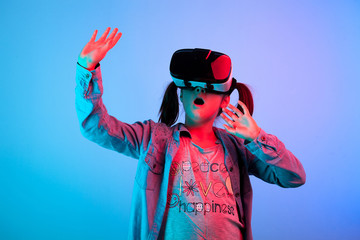 Amazed young girl experiencing virtual reality with a VR headset on the head